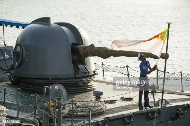 A sailor raises a Sri Lankan national flag aboard the Sri Lanka Navy's SLNS Sagara P/N 622 Sukanya Class ship at the IMDEX Asia 2017 maritime defence...