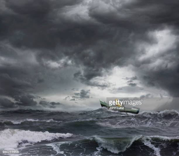 sailor rowing a small boat through an ocean storm - tempesta foto e immagini stock