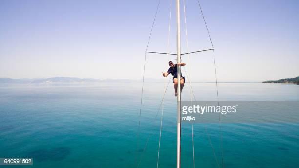 Sailor saluting from mast of sailboat