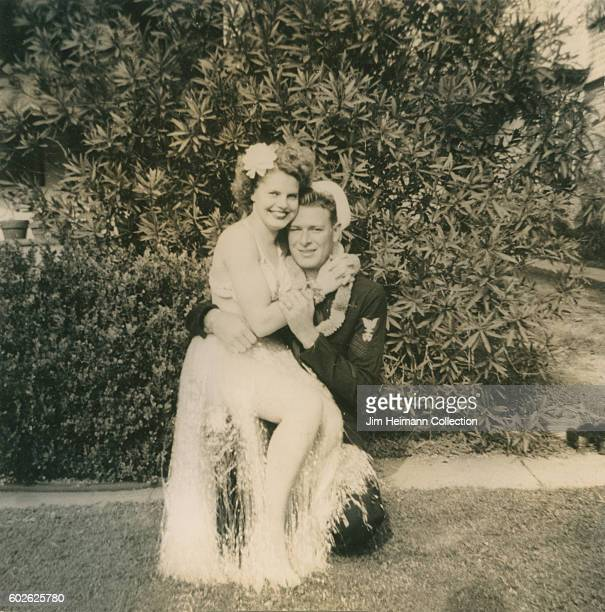 Sailor sitting with woman in hula skirt sitting on his lap outside on lawn in front of bush