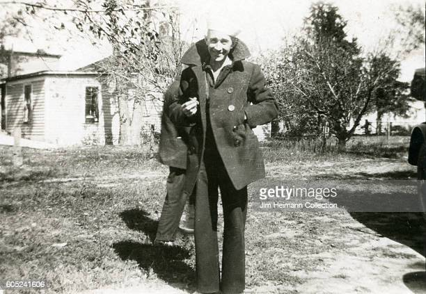 Sailor standing in grass in front of house, wearing coat. Another man in partially obscured behind im.