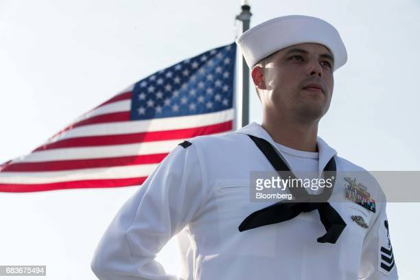 A sailor stands in front of a US national flag aboard the US Navy's USS Coronado littoral combat ship at the IMDEX Asia 2017 maritime defence show in...