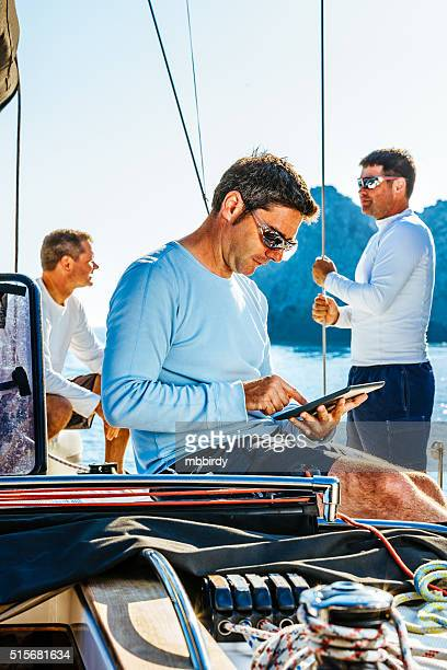 Sailor using digital tablet on sailboat