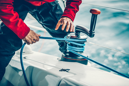 Sailor winding rope on winch with hands 1164848801