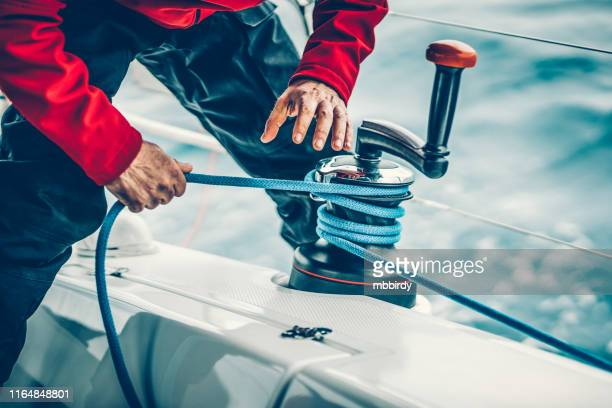 sailor winding rope on winch with hands - sailing team stock pictures, royalty-free photos & images