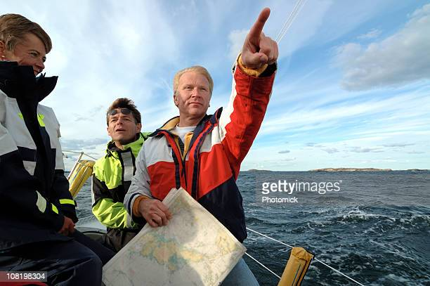 Sailor with a chart in his hand pointing forward