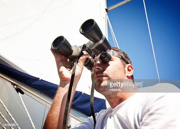 Seemann mit Fernglas auf Segelboot