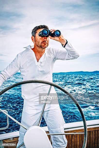 Sailor with binoculars on sailboat