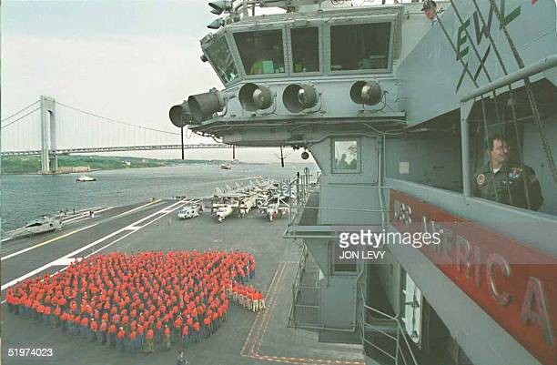 Sailors aboard the aircraft carrier USS America stand together on deck in the shape of a Big Apple upon arriving in New York at the Verrazano Bridge...