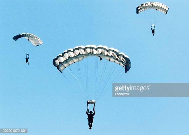 sailors and airmen parachuting during training exercise - fallschirm stock-fotos und bilder