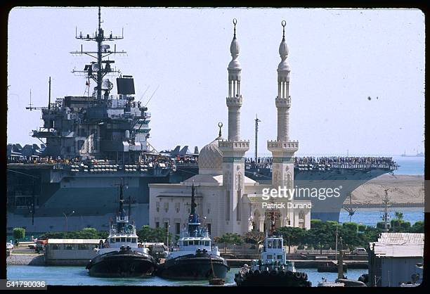 Sailors and crew crowd the flight deck of the USS Eisenhower as the enormous aircraft carrier steams past a mosque on the Suez Canal on her way to...
