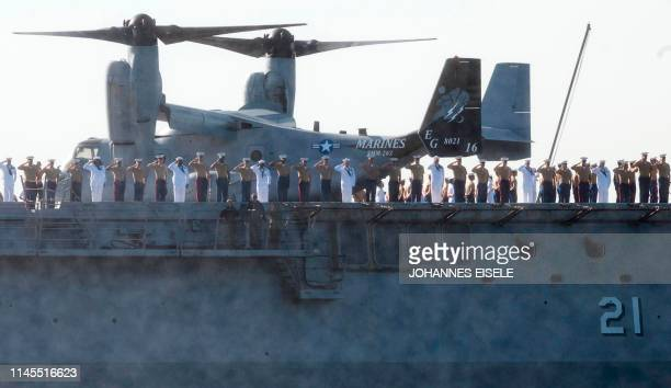 Sailors and Marines salute from the USS New York as the US Navy vessel takes part in Fleet Week 2019 on May 22 in New York