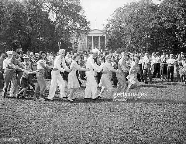 Sailors and Washington DC residents dance the conga in Lafayette Park waiting for President Truman to announce the surrender of Japan in World War II