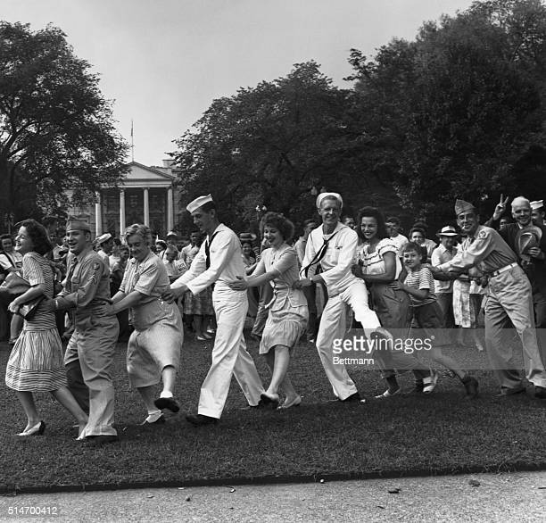 Sailors and Washington residents dance the conga in Lafayette Park waiting for President Truman to announce the surrender of Japan in World War II