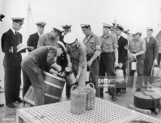 Sailors are issued with their rum ration on the HMS Torquay circa 1956