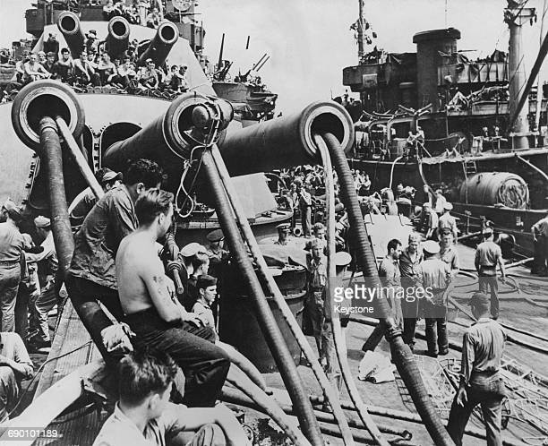 Sailors attend water pumps that have been placed down the barrels from one of the bow 14 in /45 cal guns gun turrets of the USS Pennsylvania a...