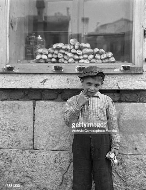A sailor's child posing for the picture holding a morsel of bread and a spoon Chioggia Venice 1950