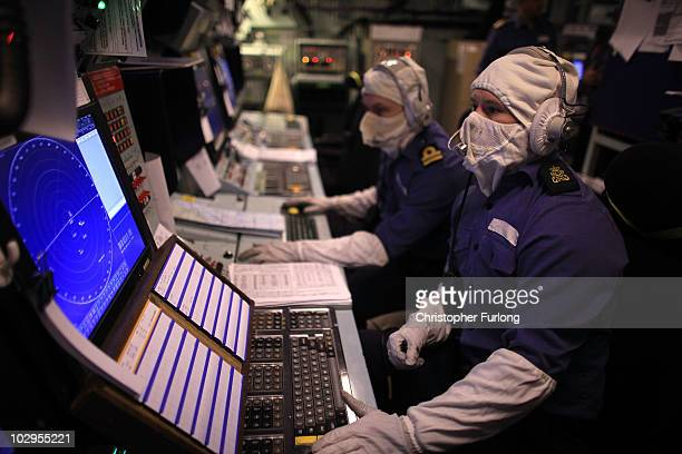 Sailors don their antiflash protection as they work in the operations room of HMS Ark Royal during Exercise Auriga on July 14 2010 at sea in Onslow...