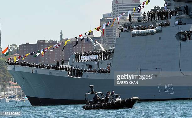Sailors from India's warship INS Sahyadri gesture towards Australia's warship HMAS Leeuwin carrying Britain's Prince Harry Australian Prime Minister...