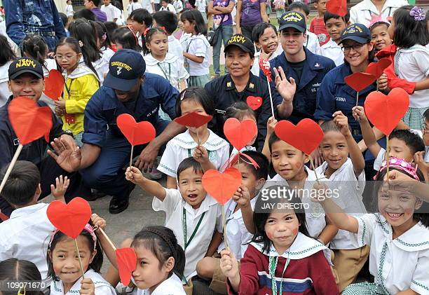 Sailors from the USS Blue Ridge and the Philippine navy have a photo oportunity with students before painting and repairing classrooms at the Sto...