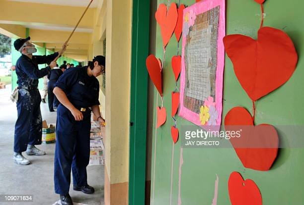 Sailors from the USS Blue Ridge and the Philippine navy paint and repair classrooms at the Sto. Nino Elementary School in Manila on February 14, 2011...
