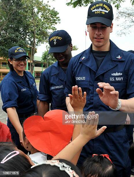 Sailors from the USS Blue Ridge have a photo oportunity with students before painting and repairing classrooms at the Sto Nino Elementary School in...