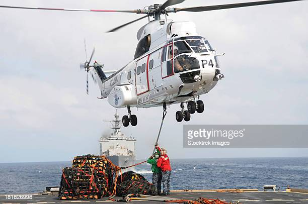 sailors hook up a pole pendant to a sa-330j puma helicopter. - landing touching down stock pictures, royalty-free photos & images