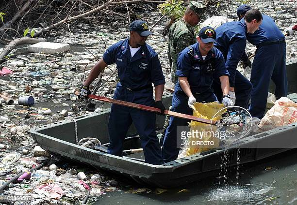 US sailors in blue coveralls from the visiting aircraft carrier USS George Washington join their Filipino counterparts in cleaning a heavily polluted...