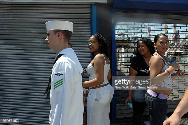 Sailors in Coney Island AOAN Joseph Bruner walks along Surf Ave past local girls