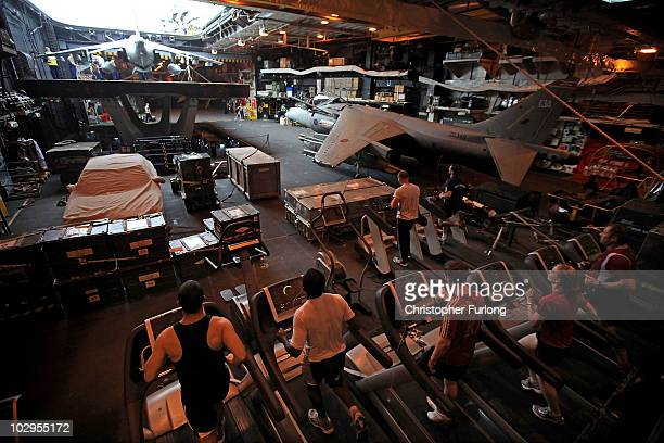 Sailors keep fit using treadmills in the hanger of HMS Ark Royal during Exercise Auriga on July 14 2010 at sea in Onslow Bay near North Carolina HMS...
