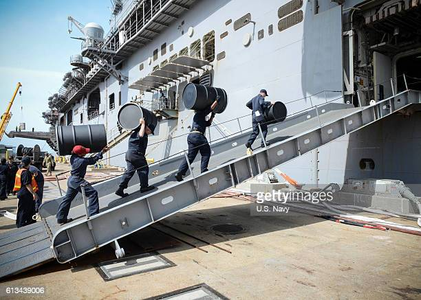 Sailors move supplies aboard the amphibious assault ship USS Iwo Jima during an onload of more than 500 Marines from the 24th Marine Expeditionary...