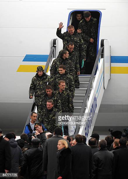 Sailors of crew member of a Ukrainian ship captured by Somali pirates disembark after after they arrived home at Kiev airport as relatives wait for...