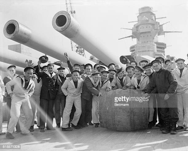 Sailors of the crew of the huge French battleship 'Richelieu' roll a barrel of wine down the deck under the deadly 15inch guns of the warship's...