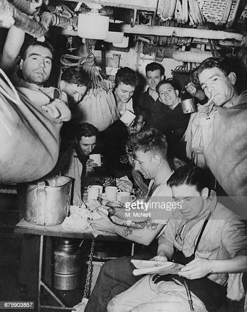 Sailors off watch in their hammocks and preparing a meal in the stokers mess deck aboard a Royal Navy convoy escort destroyer on 12 March 1943...