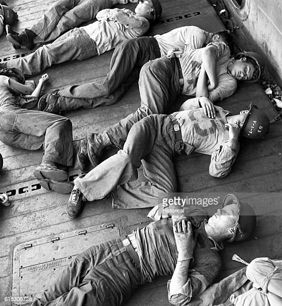 Sailors on board the USS Lexington rest after more than twentyfour hours at general quarters December 5 1943 | Location USS Lexington
