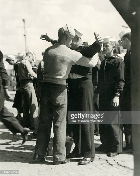 Sailors on line behind one who has arms up as another sailor frisks him