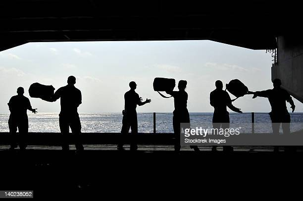 Sailors pass supplies to each other in the hangar bay of USS Ronald Reagan.
