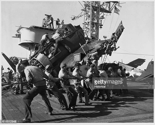 Sailors pull on ropes attached to the wreckage of a typhoondamaged aircraft aboard the USS Altamaha