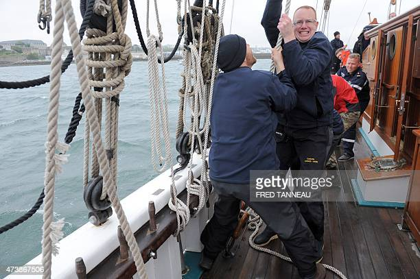 Sailors pulls a rope aboard schooner Etoile a sailboat of a French naval school on May 18 2015 at the military port of Brest western France The...