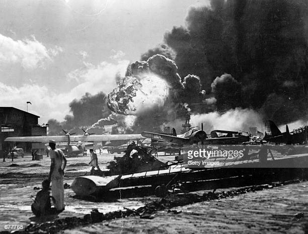 US Sailors stand amid wreckage watching as the USS Shaw explodes December 7 1941 on Ford Island Pearl Harbor Hawaii during the Japanese attack...