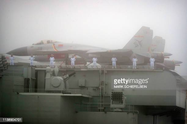 Sailors stand near fighter jets on the deck of the Chinese People's Liberation Army Navy aircraft carrier Liaoning as it participates in a naval...