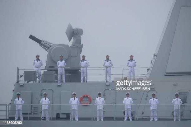Sailors stand on the deck of the new type 055 guide missile destroyer Nanchang of the Chinese People's Liberation Army Navy as it participates in a...