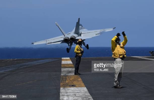 Sailors stand on the flight deck while an FA-18 hornet fighter jet takes off, during a routine training aboard US aircraft carrier Theodore Roosevelt...