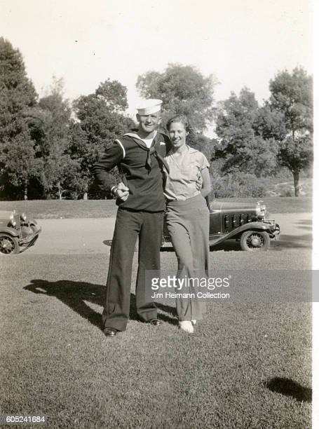 Sailors standing with his arm around a woman Parked cars in trees behind them