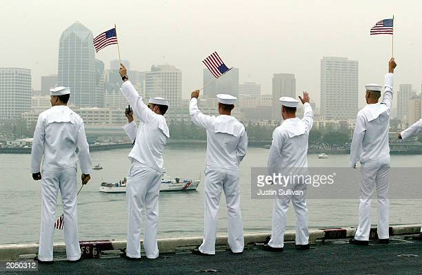 S sailors wave to a passing boat while manning the rails on the USS Constellation as they return home June 2 2003 in Coronado California The...