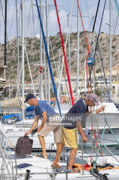 sailors working on a yatch in cesme marina on a sunny autumn day. - emreturanphoto stock pictures, royalty-free photos & images