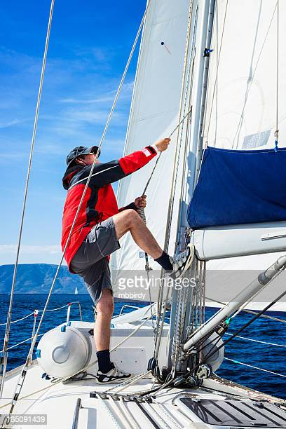 Sails up, sailor is hoisting the mainsail