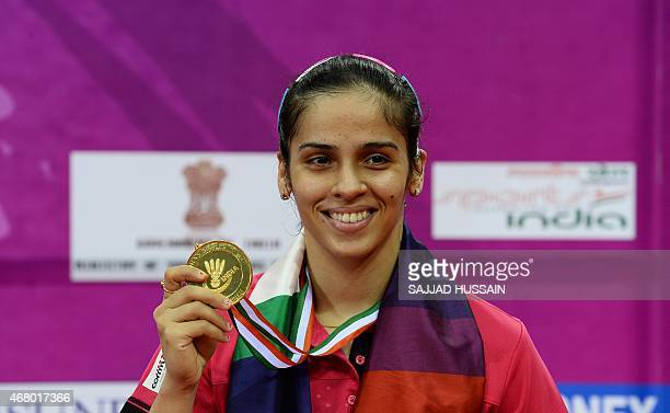 Saina Nehwal of India displays her gold medal after winning her women's singles final match against Ratchanok Intanon of Thailand at the Yonex...