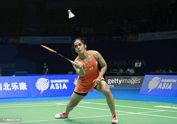 Saina Nehwal of India hits a return against Han Yue of China during their women's singles first round match at the 2019 Badminton Asia Championships...