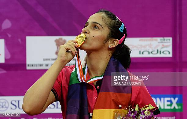 Saina Nehwal of India kisses her gold medal after winning her women's singles final match against Ratchanok Intanon of Thailand at the Yonex Sunrise...